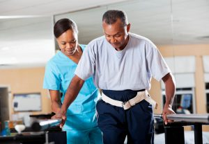 nursing helping patient with physical therapy