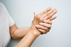 Elderly woman holding her arthritic hands