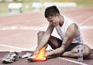 young athlete holding his leg in pain